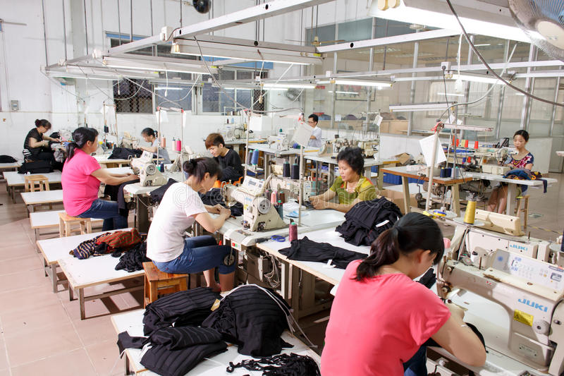 Worker in a chinese garment factory. Dongguan Guangdong, China - June 4, 2013: a group of Workers in a chinese garment factory working at workshop