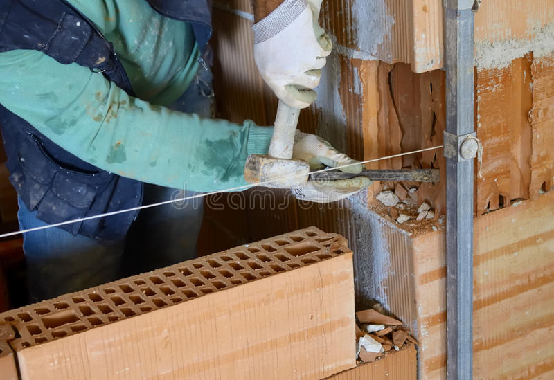 Worker with chisel on an internal wall stock image