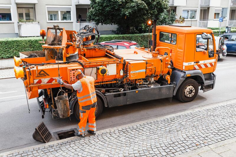 Worker of the city utility service clears storm sewer runoff from clogging. 06 August 2019, Munchen, Germany: Worker of the city utility service clears storm royalty free stock photo