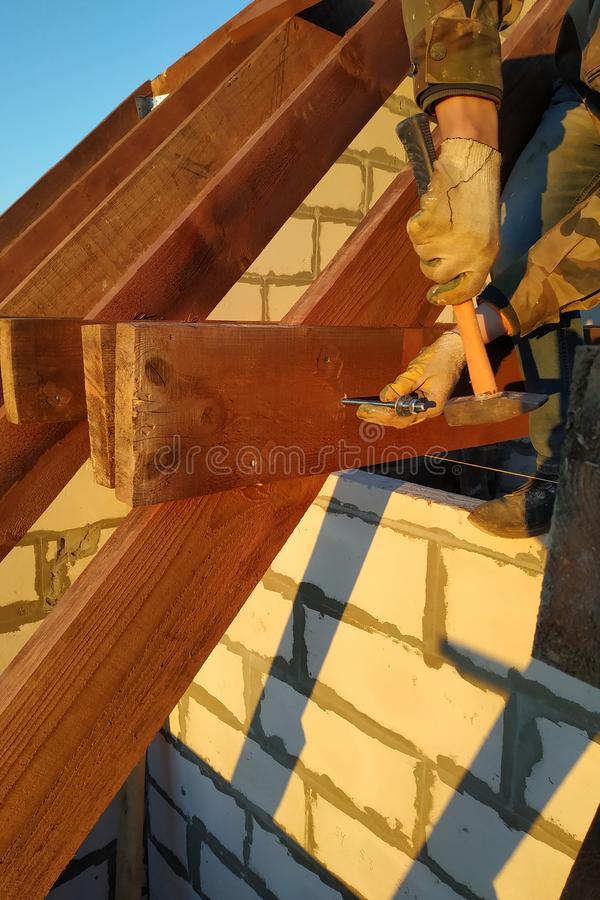 The worker claps the studs with a hammer on the rafters, building a roof stock images