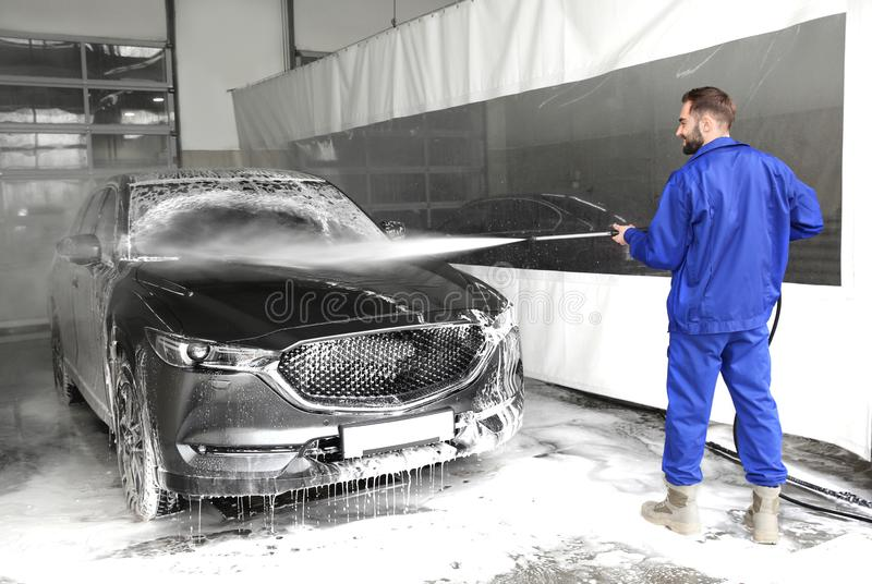 Worker cleaning automobile at car wash. Worker cleaning automobile with high pressure water jet at car wash stock photo