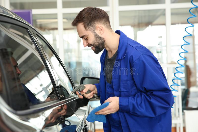 Worker cleaning automobile with gun and rag. At car wash stock photos