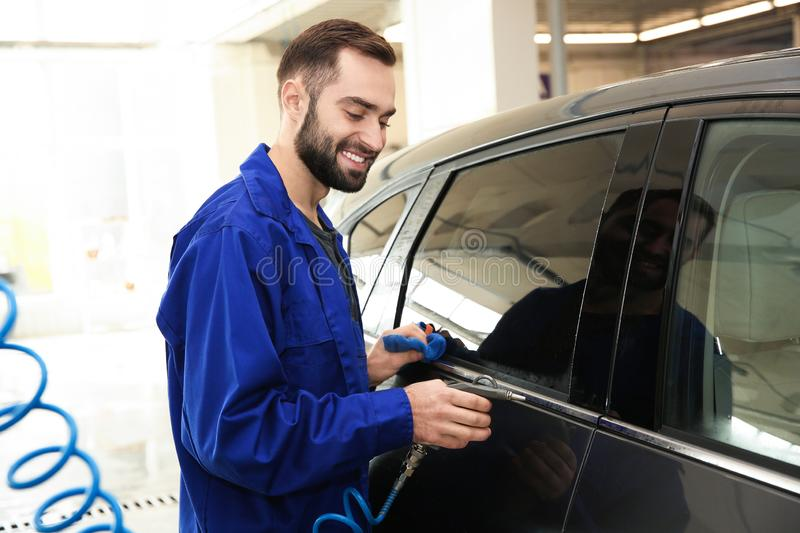 Worker cleaning automobile with gun and rag. At car wash stock images