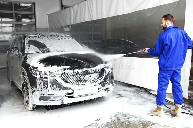 Worker cleaning automobile with high pressure water jet. At car wash stock photography