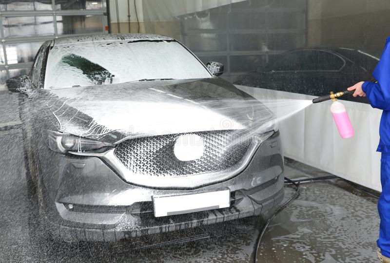 Worker cleaning automobile with high pressure water jet. At car wash royalty free stock image