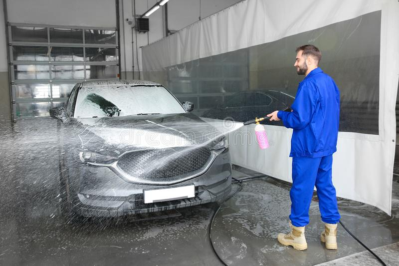 Worker cleaning automobile with high pressure water jet. At car wash stock images
