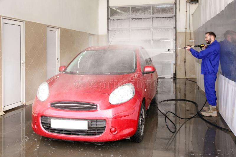 Worker cleaning automobile with high pressure water jet. At car wash royalty free stock photos