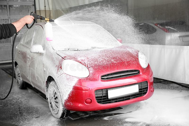 Worker cleaning automobile with high pressure water jet stock images