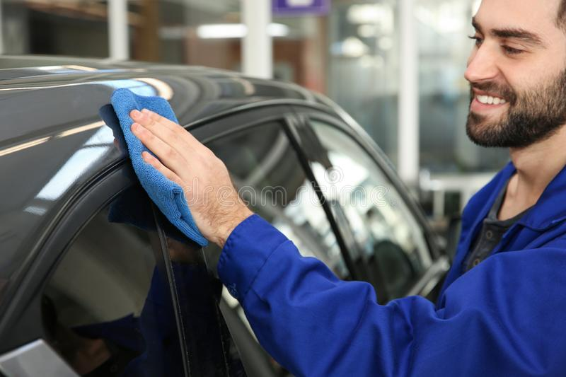 Worker cleaning automobile with rag. At car wash royalty free stock photos