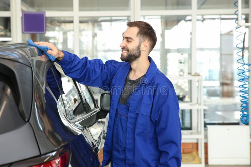 Worker cleaning automobile with rag. At car wash stock photo