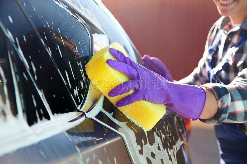 Worker cleaning automobile with sponge at car royalty free stock image