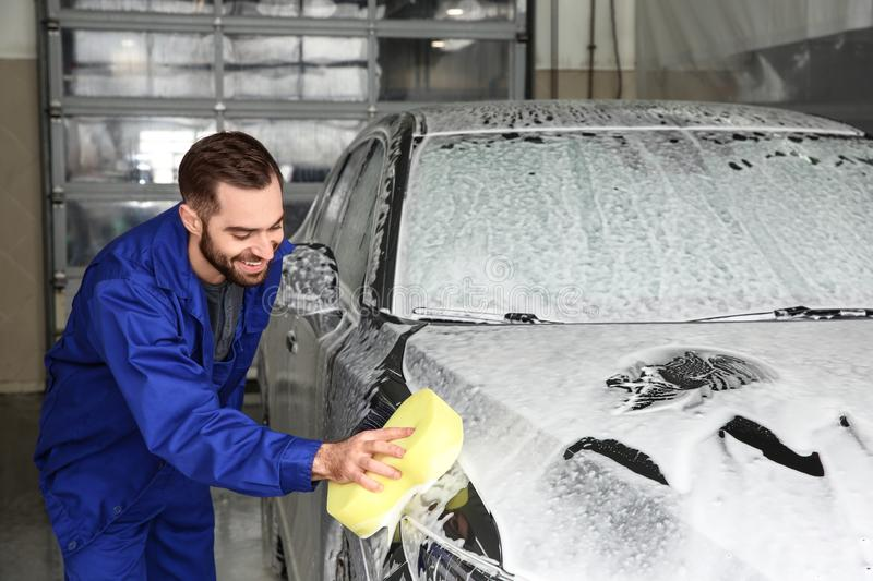 Worker cleaning automobile with sponge at car wash. Worker cleaning automobile with sponge at professional car wash royalty free stock images