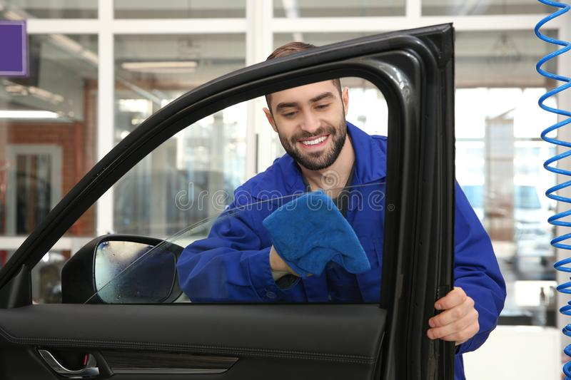 Worker cleaning automobile window glass with rag. At car wash royalty free stock image