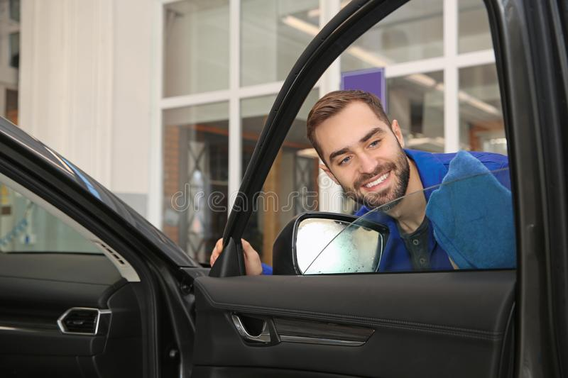 Worker cleaning automobile window glass with rag. At car wash stock images