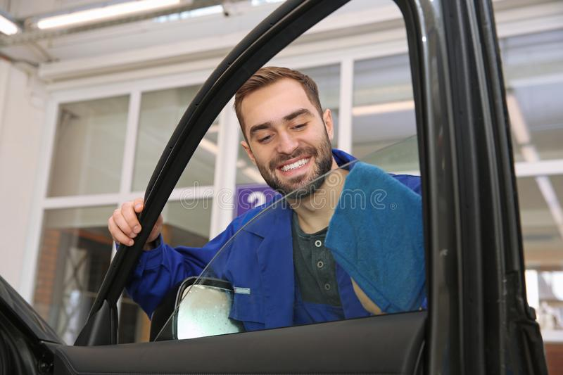 Worker cleaning automobile window glass with rag. At car wash stock image