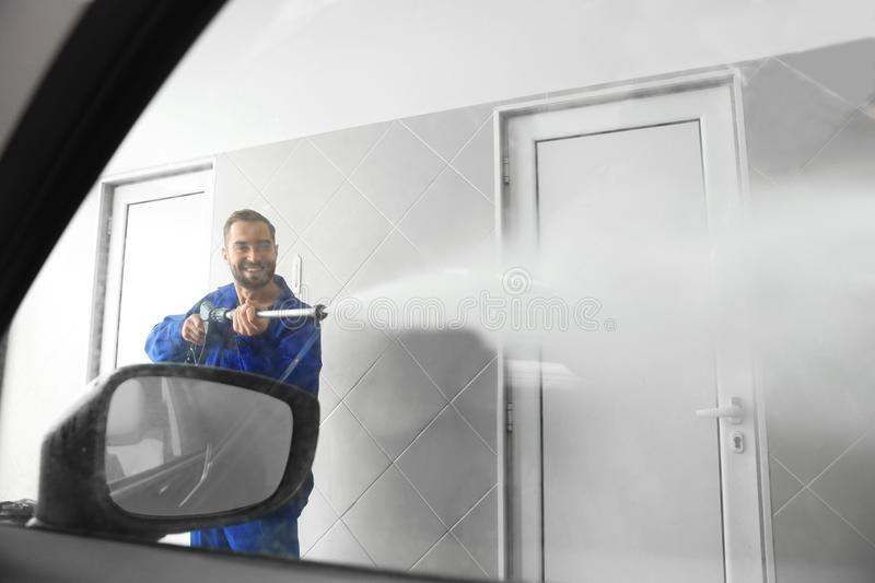Worker cleaning automobile window with high pressure water jet at car wash. View from inside stock photos