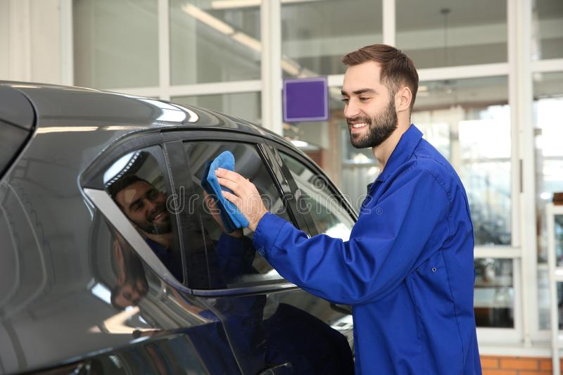 Worker cleaning automobile window with rag. At car wash royalty free stock photography