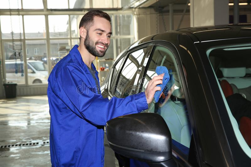 Worker cleaning automobile window with rag. At car wash royalty free stock photos