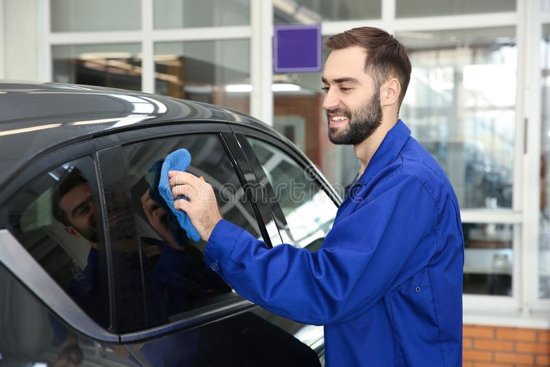 Worker cleaning automobile window with rag. At car wash stock image