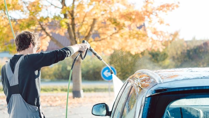 Worker cleaning car with high pressure water nozzle stock photography