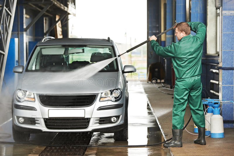 Worker Cleaning Car With Pressured Water Stock Photo