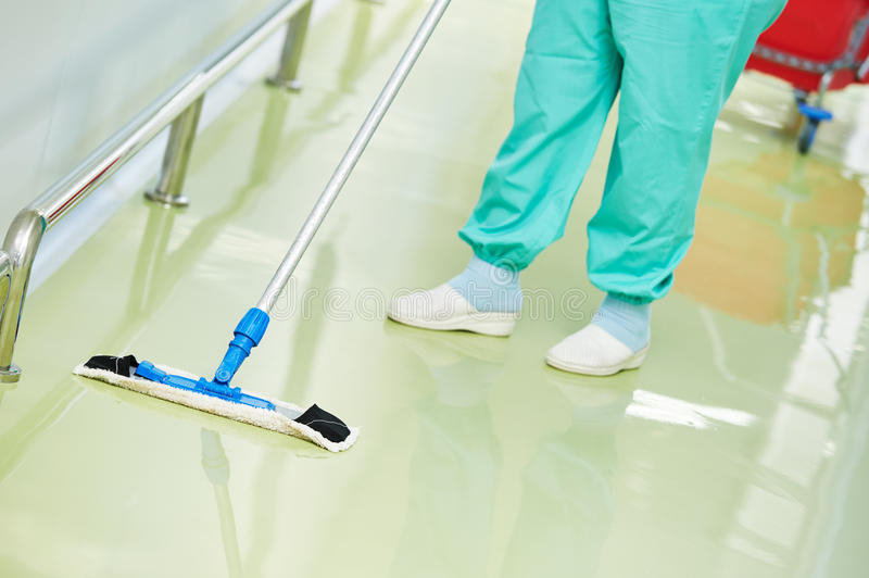 Worker cleaning floor with machine. Floor care and cleaning services with washing mop in sterile factory or clean hospital royalty free stock photos