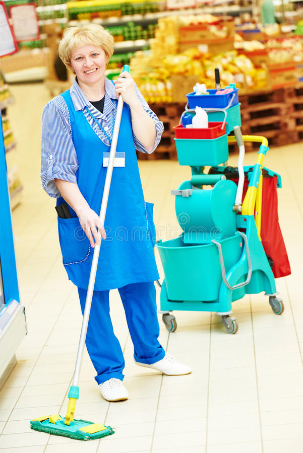 Worker cleaning floor with mop. Floor care and cleaning services with mop in supermarket shop store stock photo