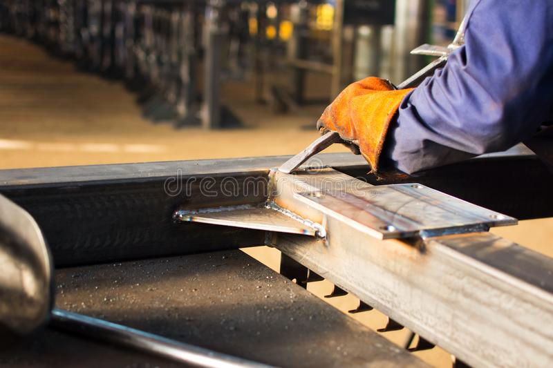 Worker cleaning fresh welded steel bar. Worker cleaning fresh welded stainless steel bar royalty free stock images