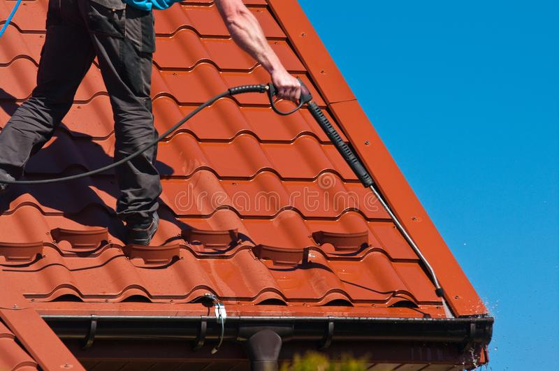 Worker cleaning metal roof with high pressure water. Detail of house maintenance: a worker cleaning metal roof with high pressure cleaner stock image