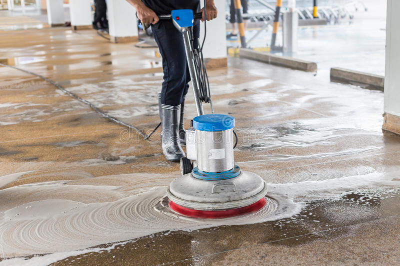 Worker cleaning sand wash exterior walkway using polishing machine and chemical or acid stock photo