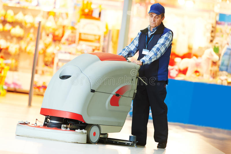 Worker cleaning store floor with machine. Floor care and cleaning services with washing machine in supermarket shop store stock photos