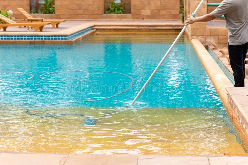 Worker cleaning swimming pool with vacuum tube in the morning. royalty free stock photos