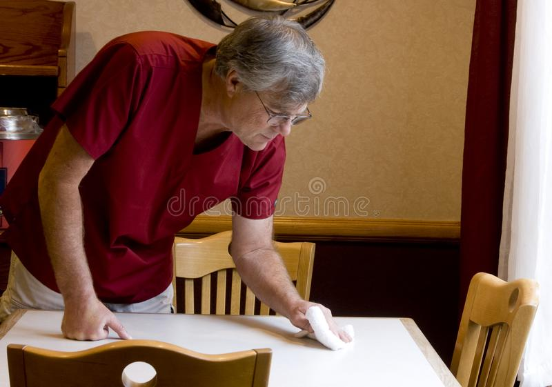 Worker cleaning a table royalty free stock photography