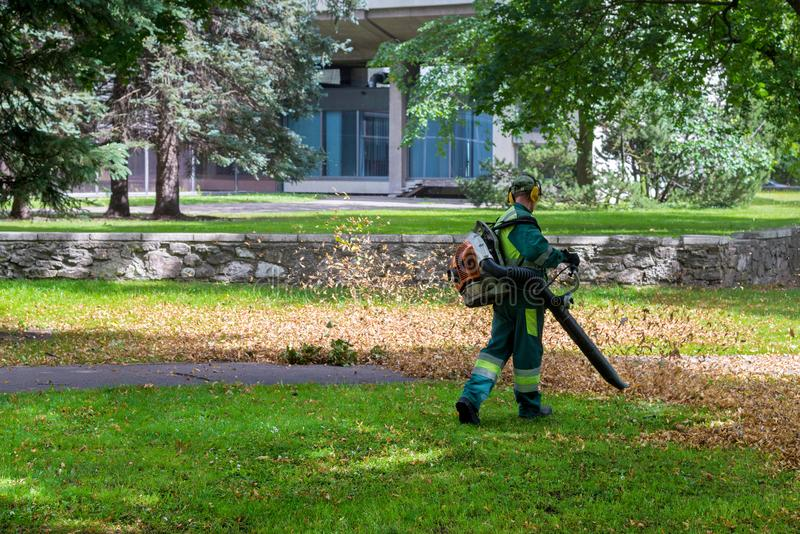 Worker is cleaning up in the city park using leaf blower tool royalty free stock images