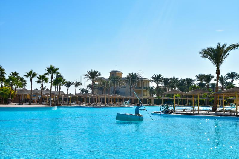 Worker cleans the pool in a hotel in Egypt royalty free stock image