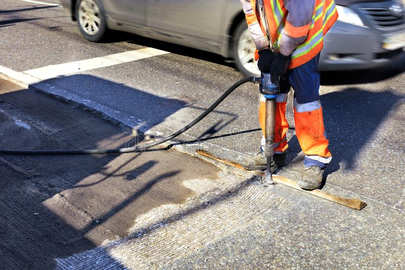 A worker clears a piece of asphalt with a pneumatic jackhammer in road construction stock images