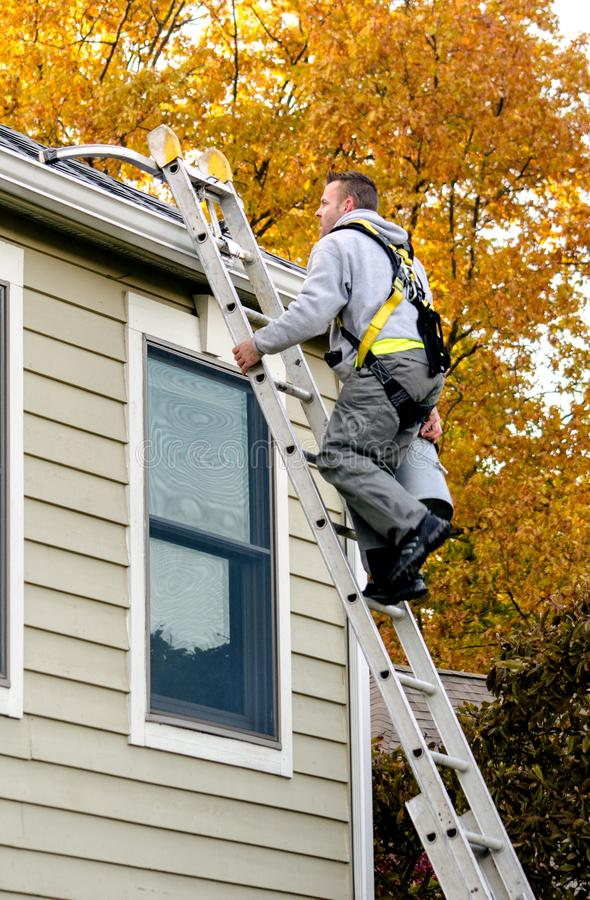 Worker climbing ladder to clean gutters stock photography