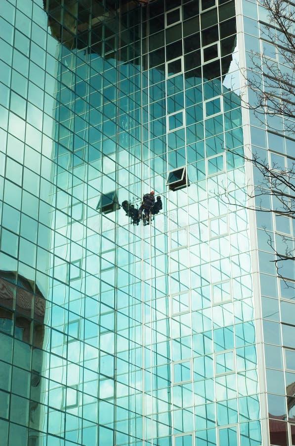 Worker climbing at mirror wall stock image
