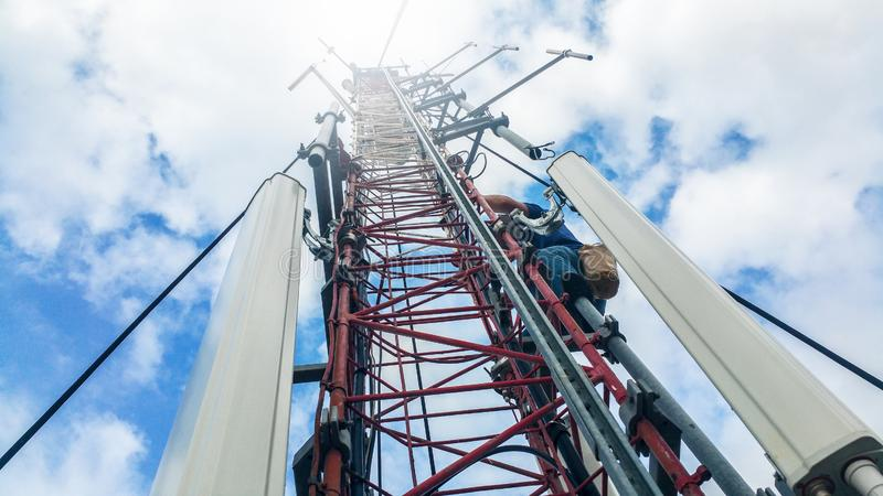 Worker climbing on a very high metal construction radio cellular network antenna base station royalty free stock image