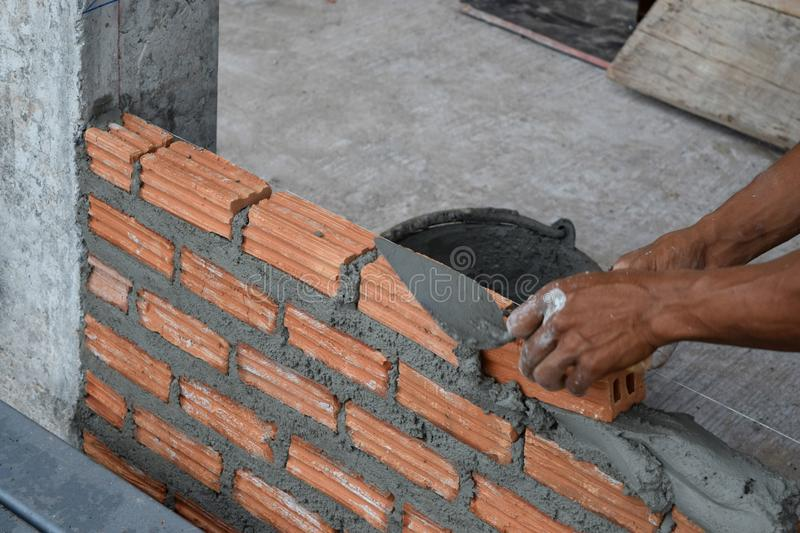 Worker in Close up of industrial bricklayer installing bricks and mortar cement brick royalty free stock photos