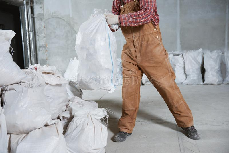 Worker collecting construction waste in bag stock images