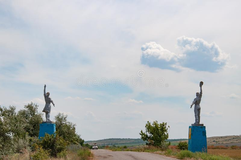 Silhouettes of Worker and Kolkhoz Woman style statues by roadsides. Social realism monuments in countryside of Ukraine. stock photos