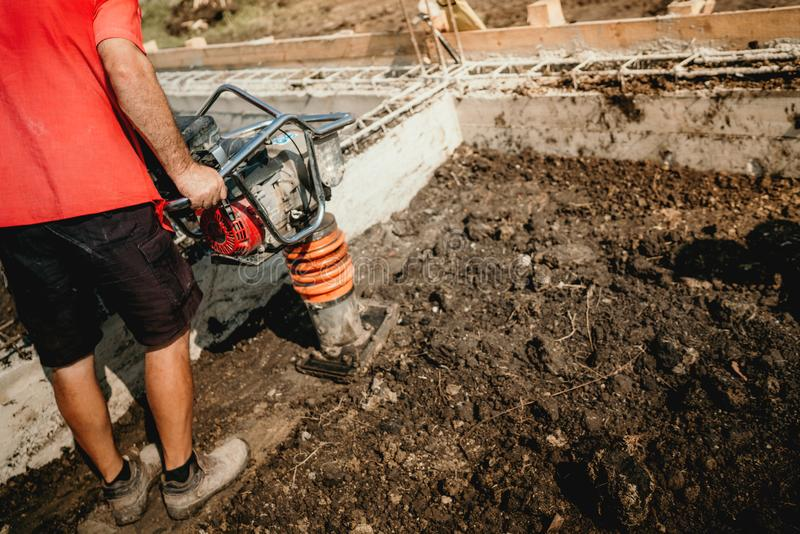worker compacting soil with vibration compaction machine during foundation works royalty free stock image