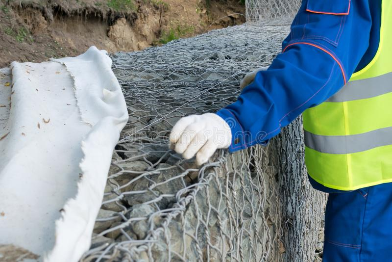 A worker in construction clothing covers a stone structure with a special cloth royalty free stock photography