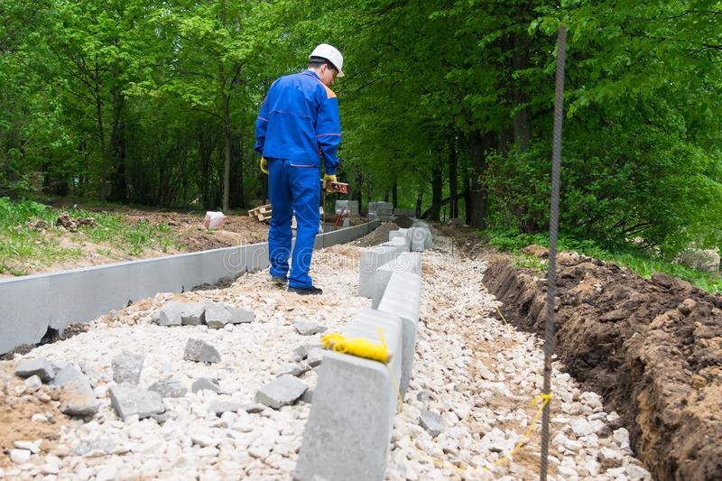 Worker on the construction of a new pedestrian road in a city park stock photos