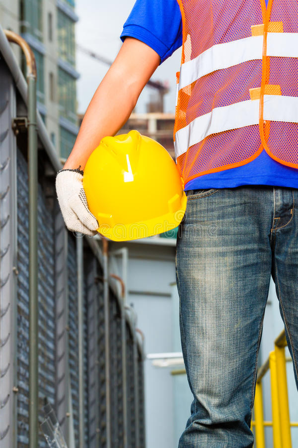 Worker on construction site with helmet or hard hat stock photography