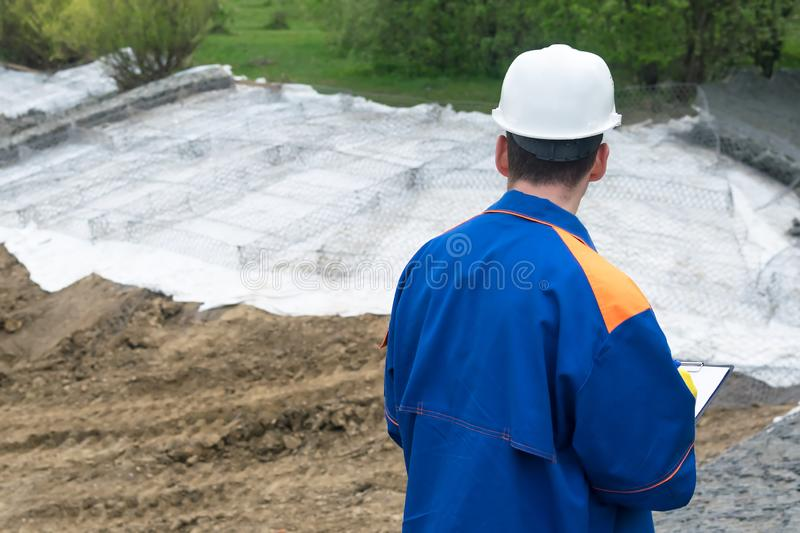 Worker at the construction site looks at the construction plan makes notes in the tablet, the view from the rear royalty free stock photos