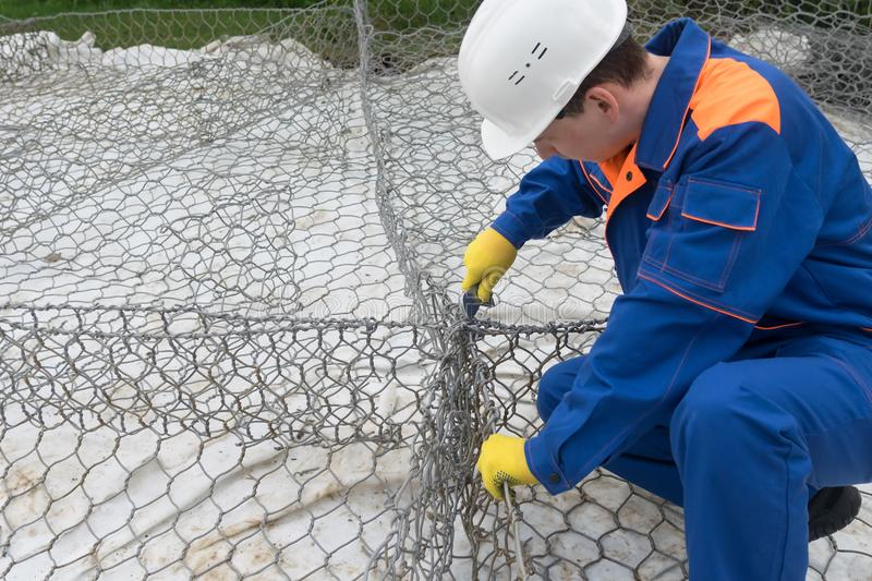 Worker on a construction site in a white helmet makes the construction of iron wire, top view, close-up stock photography
