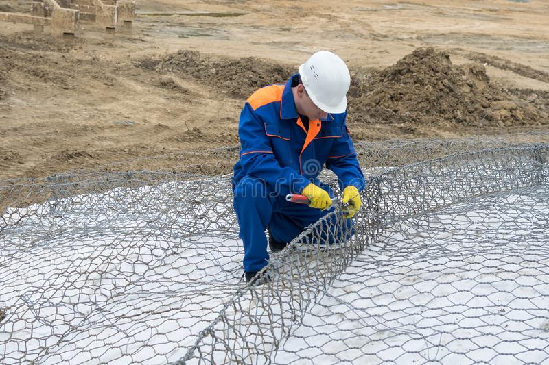Worker at a construction site in a white helmet makes a construction of iron wire, side view royalty free stock photography
