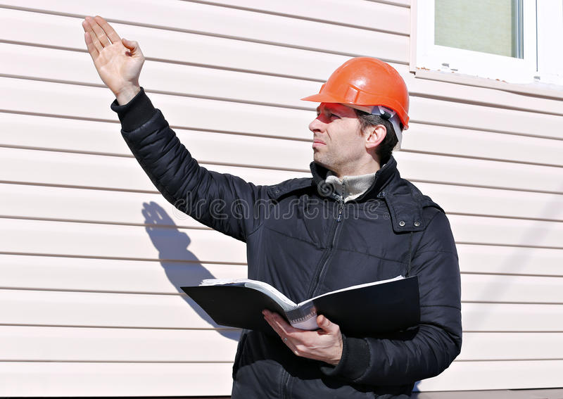 Worker on a construction site in winter looks at the drawing. And compares the work done and gives instructions gestures royalty free stock image